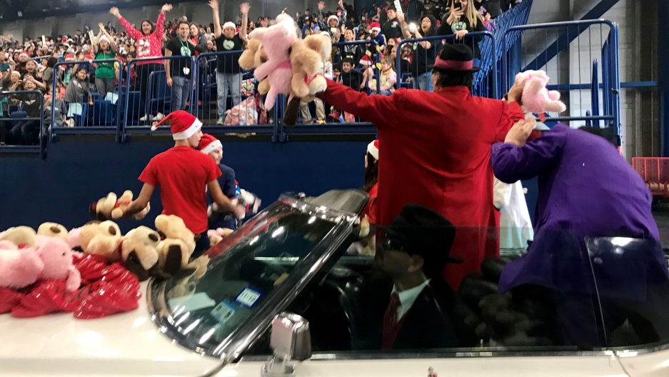 Pancho Claus is shown in a red jacket and black hat with his hands out stretch and holding stuffed animals.