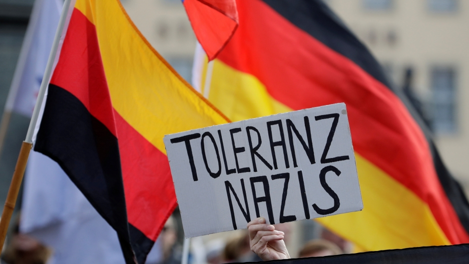 "a German flag waves and a protester holds up a sign that says ""tolerance Nazi"""