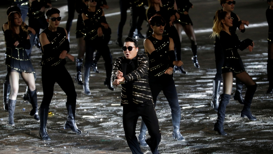 A man wears a black shiny outfit and performs with backup dancers