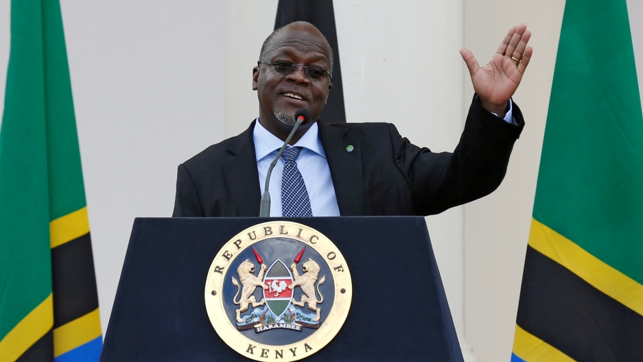 President Magufuli stands in front of a podium.