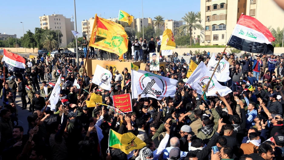 A large group of protesters are shown carrying several different flags outside of the khaki-colored walls of US Embassy in Iraq.