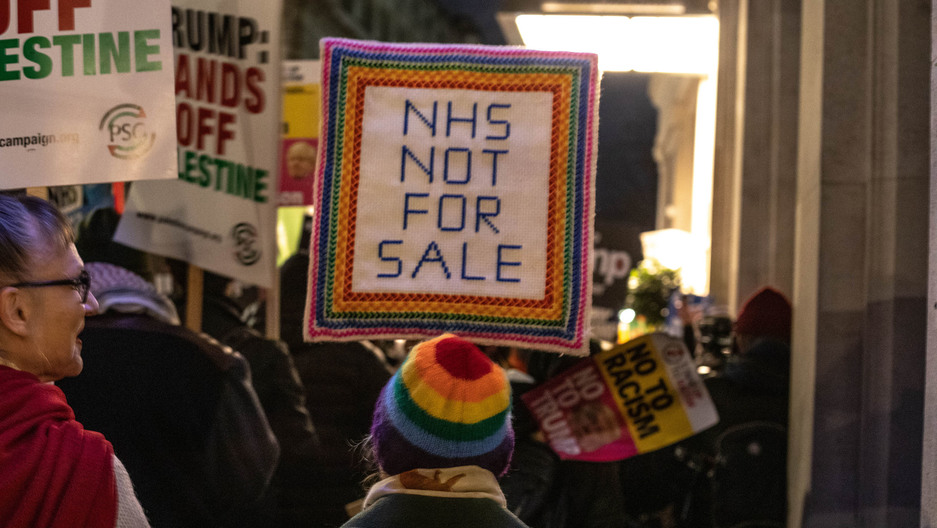 "A protester stands with a sign reading ""NHS NOT FOR SALE"""