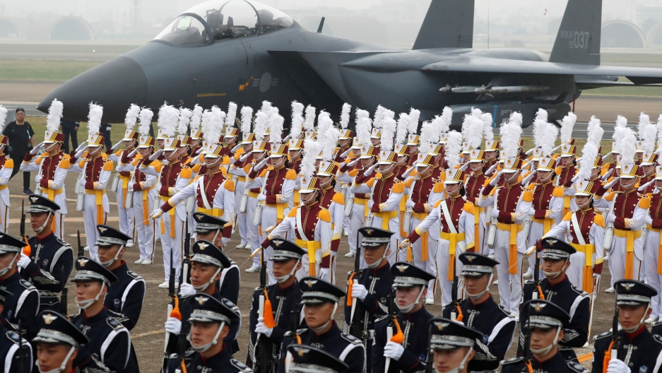 Rows of military men in white and black uniforms line up perfectly in front of a gray airplane