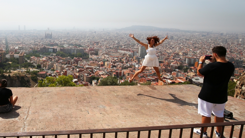 A tourist leaps in the air with a backdrop of the skyline of Barcelona