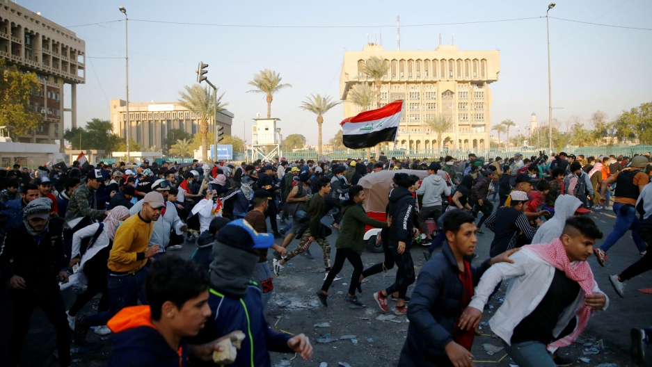 Iraqi demonstrators run for cover as they clash with Iraqi security forces