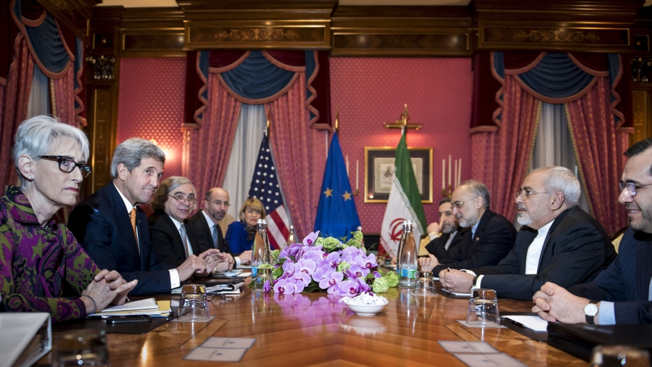 Men and women sit around a negotiating table with flags in the background.