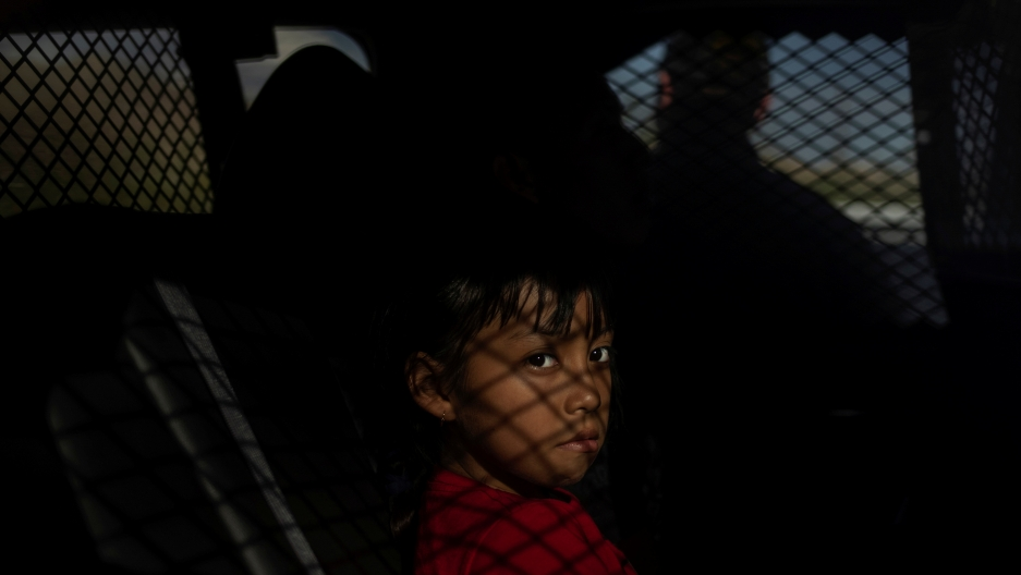 A 9-year-old migrant girl from Guatemala sits in the back of a US Border Patrol vehicle after she was apprehended for crossing the border from Mexico in Sunland Park, New Mexico, on June 14, 2018.