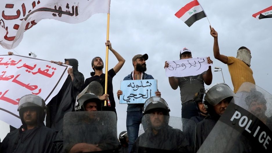 Iraqi policemen stand in front of demonstrators during a protest over corruption, lack of jobs, and poor services, in Kerbala, Iraq, on October 25, 2019.