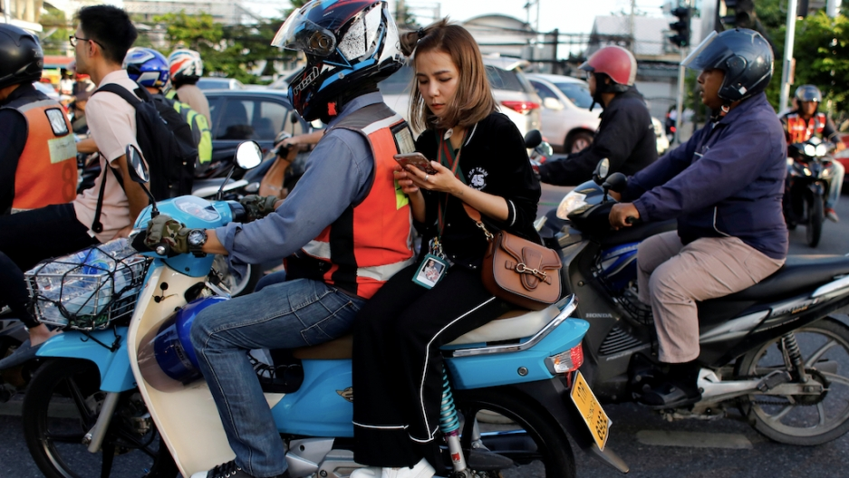 A woman checks her phone while riding on the back of a motorbike.