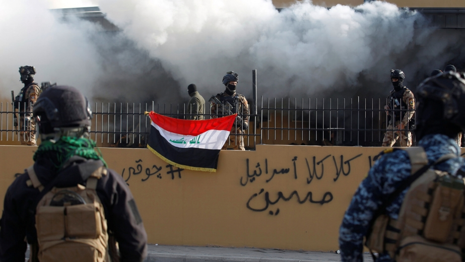 Several Iraqi security authorities are shown standing guard behind a metal fence with smoke billowing out from the US Embassy behind them.