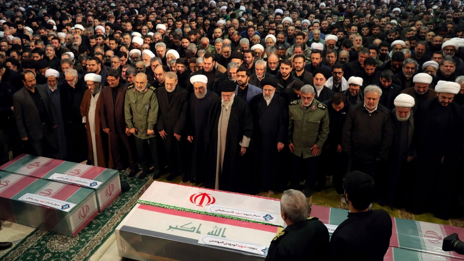 Iran's Supreme Leader Ayatollah Ali Khamenei and President Hassan Rouhani are shown in front of a large group of people with their heads bowed and praying.