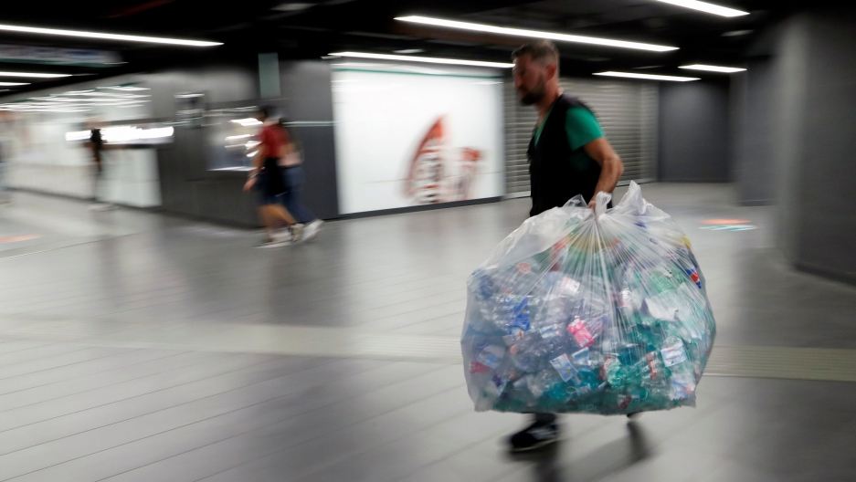 A man is shown wearing a dark-color vest and carrying a large garbage bag full of plastic bottles.