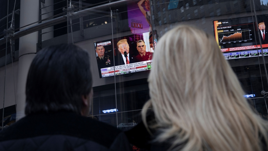 Two people are shown from behind looking up at television monitors showing US President Donald Trump.