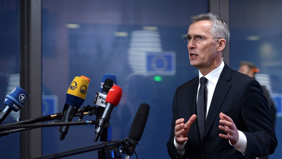 NATO Secretary General Jens Stoltenberg is shown wearing a dark suit and standing in front of several microphones.