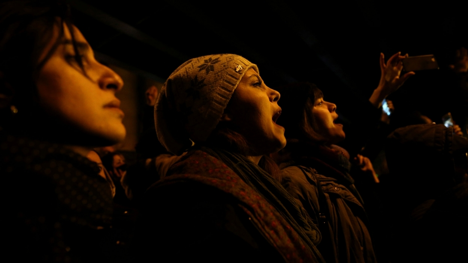 Several people are shown with their mouths agape and shouting in the dark of the night.