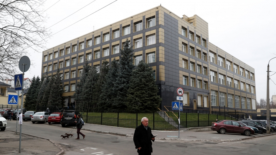 A man with two dogs is shown walking past a five story building in Kyiv, Ukraine.