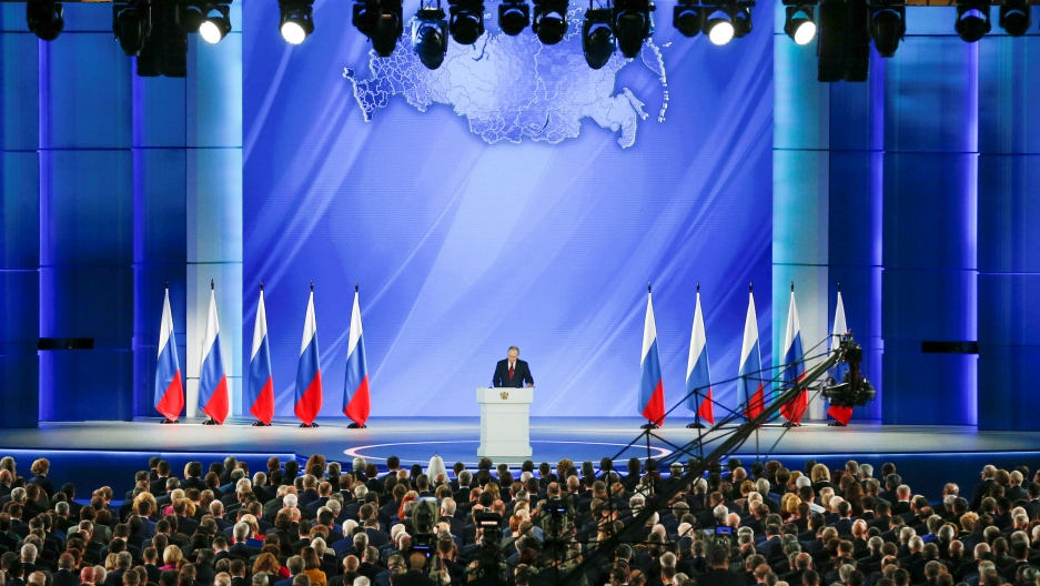 Russian President Vladimir Putin is shown standing on a large stage with several Russian flags behind him.