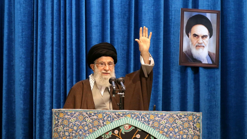 Iran's Supreme Leader Ayatollah Ali Khamenei his shown standing at a podium with his hand raised.