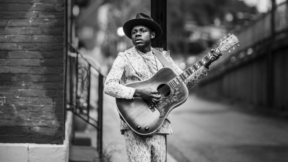 A man wearing a hat plays a guitar