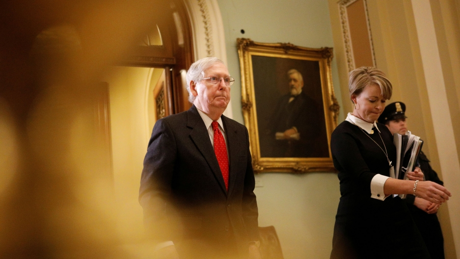 US Senate Majority Leader Mitch McConnell is shown wearing a dark suit and red tied walking.
