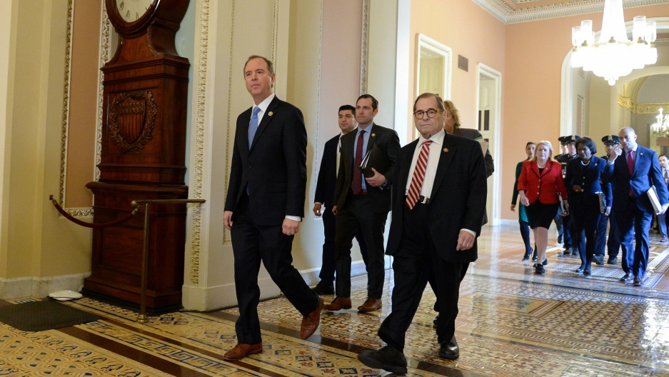 A group of lawmakers are shown wearing dark suits and walking on a marble floor.