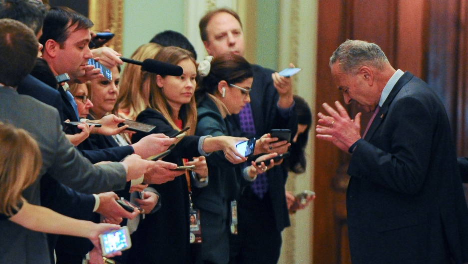 US Senate Minority Leader Chuck Schumer is shown with his hands raised and head down with a row of reporters standing across from him.