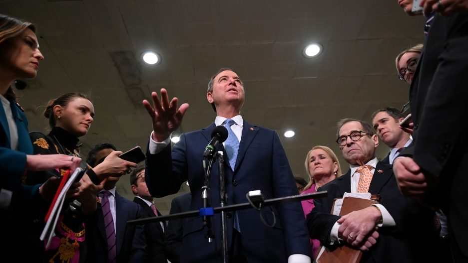 US House of Representatives Intelligence Committee Chairman Adam Schiff is shown in a photo shot from below with his right hand out and standing in front of a microphone.