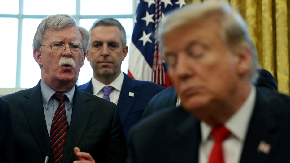 US President Donald Trump is shown in soft focus in the near ground as John Bolton speaks  from behind him.