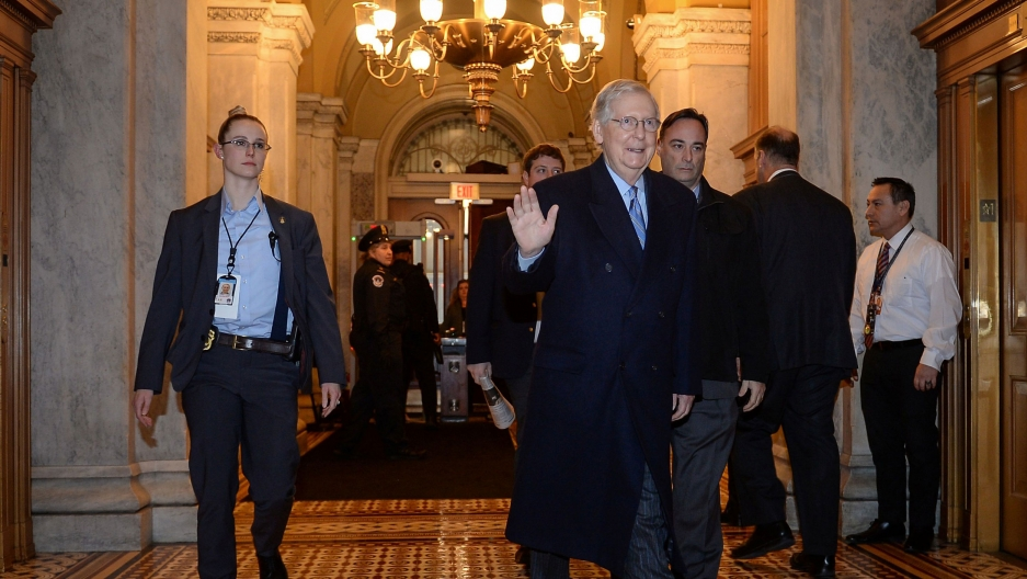 Senate Majority Leader Mitch McConnell is shown walking with security personel and weaing a dark overcoat.