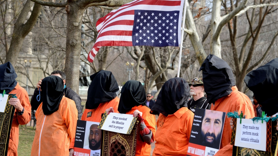 Protesters wear orange suits and black cloth over their heads with an upside down US flag behind them