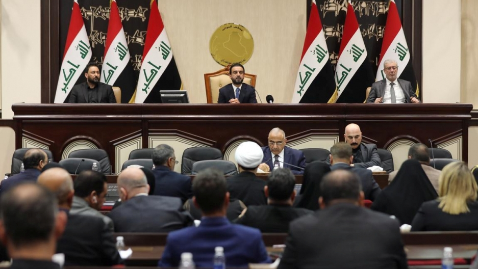 Iraqi flags wave behind a group of men in parliament