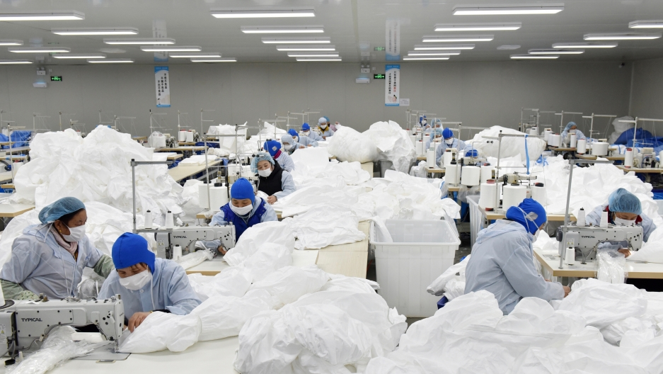 Workers make protective suits at a factory, as the country is hit by an epidemic of the new coronavirus, in Chaohu, Anhui province, China.