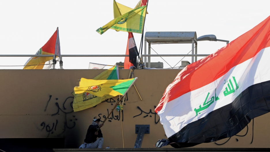 A member of Hashd al-Shaabi waves a flag
