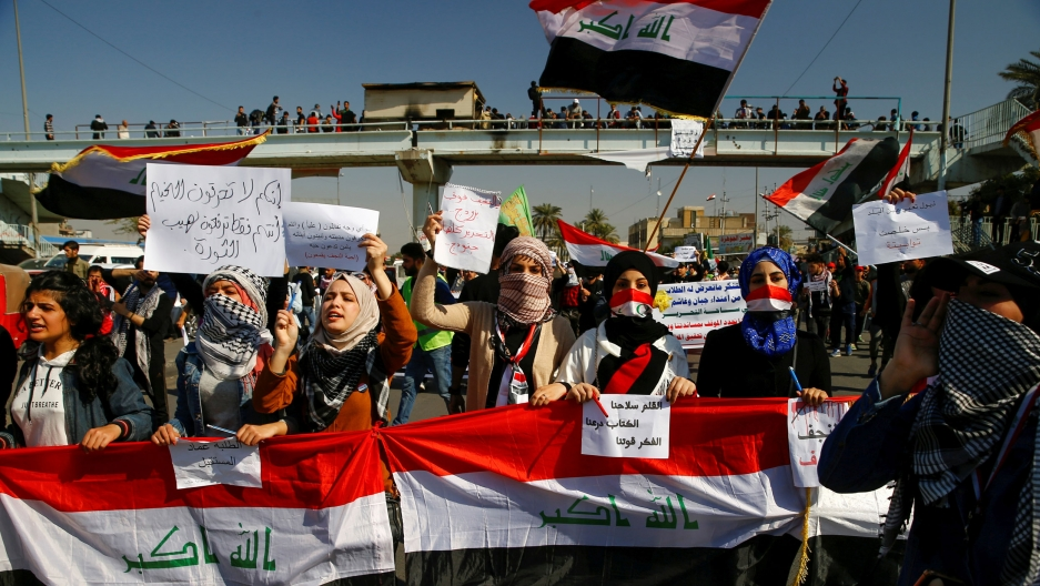 University students hold banners as they gather during ongoing anti-government protests in Baghdad, Iraq, Feb. 6, 2020.