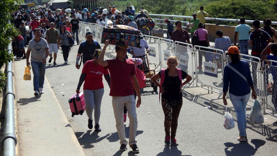 People walk across a bridge at the border with Venezuela