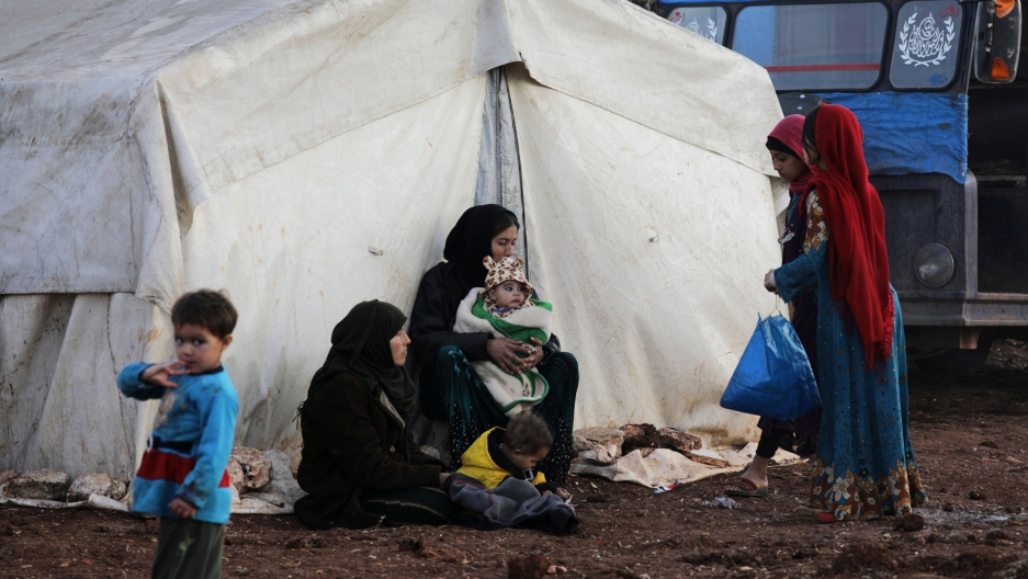 Internally displaced people stand outside tents at a makeshift camp in Azaz, Syria, Feb. 19, 2020.