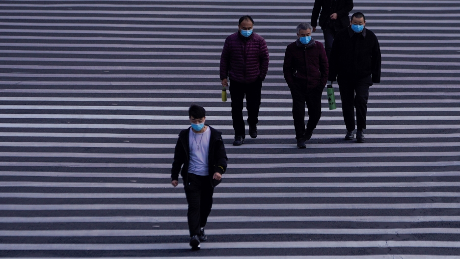Several people are shown walking on a white-lined road and wearing face masks.