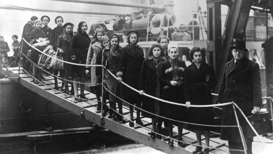 A black and white image of girls walking down a ships gangway