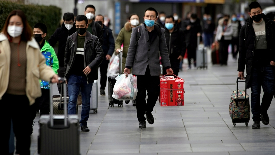 Train passengers are shown walking and wearing face masks.
