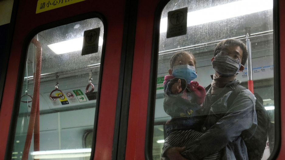 A man is shown holding a child, both wearing face masks, and shown through the window of a train.
