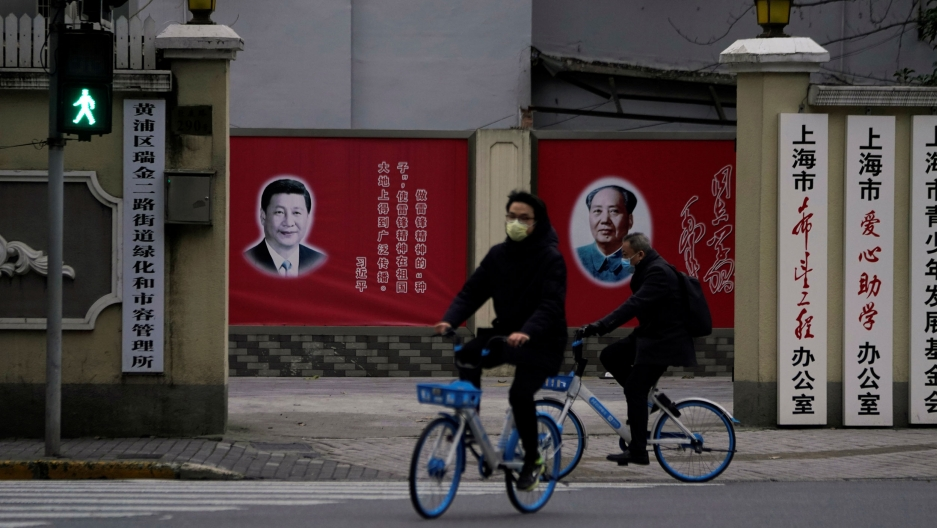 Two people riding bicycles are shown wearing face masks and passing by portraits of Chinese President Xi Jinping and late Chinese chairman Mao Zedong.