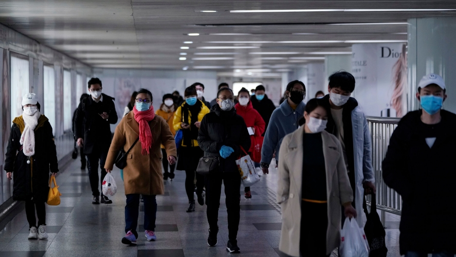 A group of people are shown walking and wearing face masks.