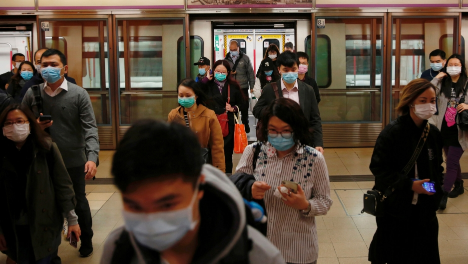 A large group of people are shown exiting a subway train, all wearing blue surgical masks.