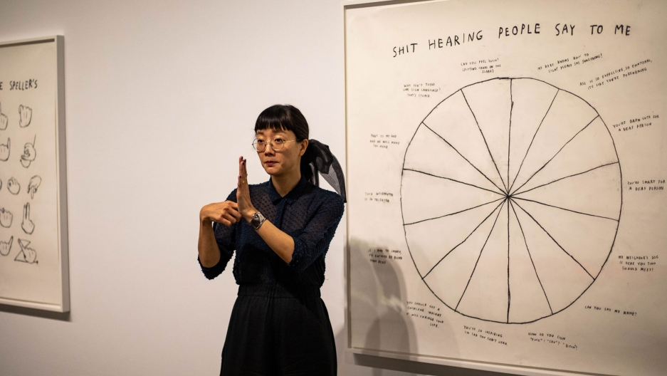 "Christine Sun Kim is shown signing and standing in front of her art featuring a pie chart titled ""Shit Hearing People Say To Me."""