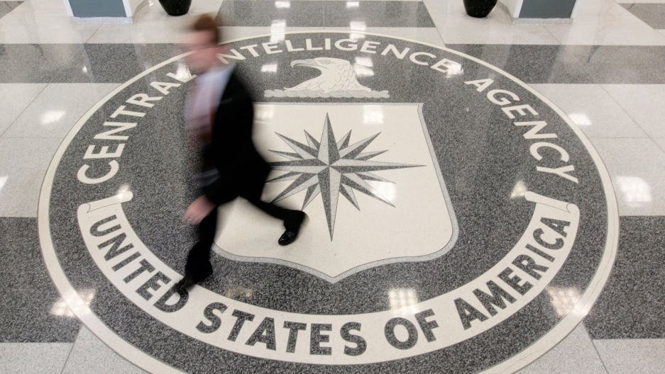 A seal of the CIA is shown from above with a person walking over it in blurred focus.