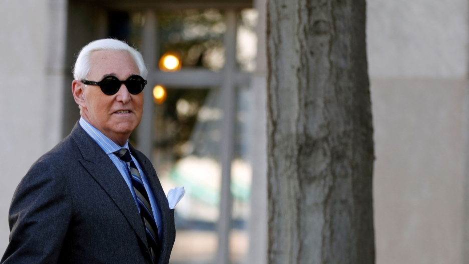 Roger Stone is shown wearing a grey suit and striped tie and dark circular sun glasses.