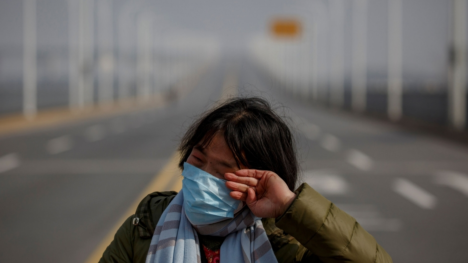 A woman is shown wearing a face mask and stripped scarf while standing on the edge of an empty bridge.