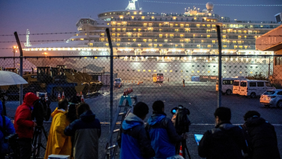 A bus arrives near the cruise ship Diamond Princess, where dozens of passengers were tested positive for coronavirus, at Daikoku Pier Cruise Terminal in Yokohama, south of Tokyo, Japan, on February 16, 2020.