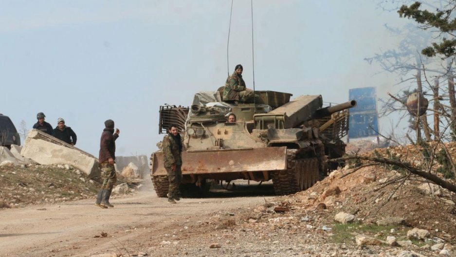 Several Syria soldiers are shown walking alongside and riding on a tank in a dirt road.