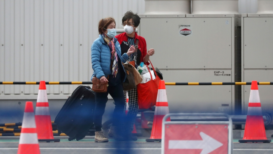 Two women are shown exiting a cruise ship wearing face masks and pulling suitcases.